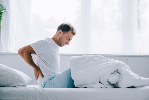 Man holding back in bed with back pain