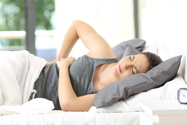 Woman with back pain in bed