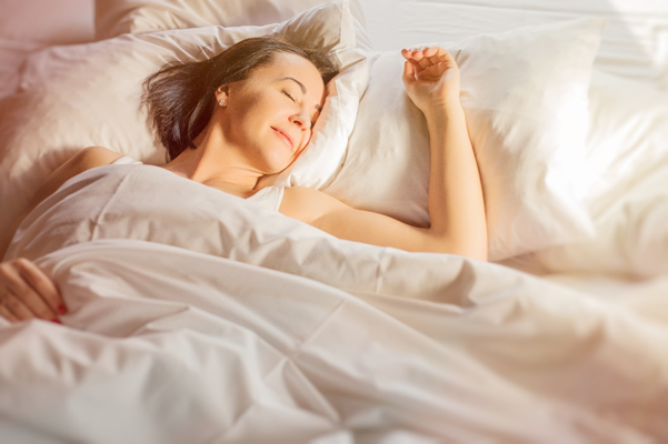 Woman enjoying comfortable sleep in bed